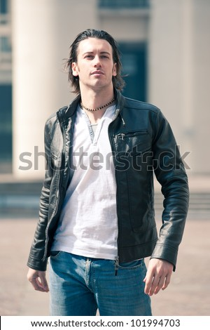 Young casual man portrait with leather jacket outdoors.