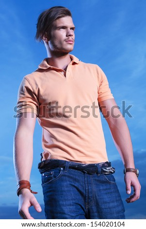 young casual man posing outdoor, looking away from the camera with the blue sky behind