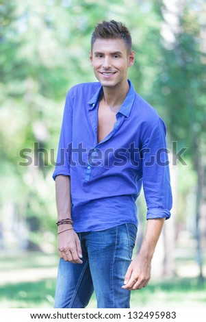 young casual man posing outdoors with a smile on his face
