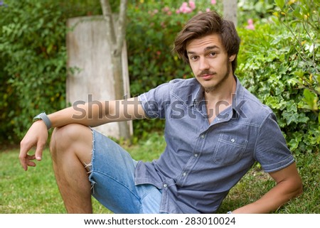 young casual man posing seated, smiling at the camera, outdoors - stock photo