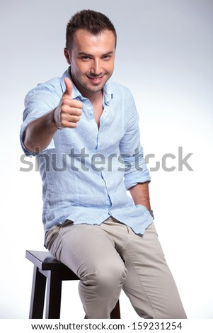 young casual man sitting on a chair and showing the thumb up gesture with a smile on his face and a hand in his pocket. on gray background - stock photo