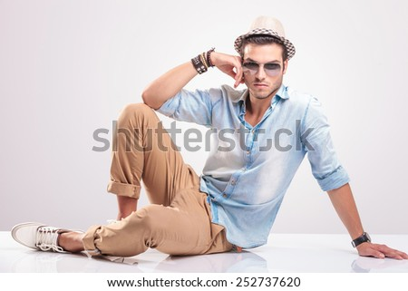 Young casual man sitting on the floor leaning his hand on his knee, looking at the camera - stock photo