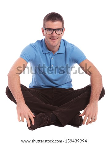 young casual man sitting on the floor with his legs crossed and smiling for the camera. on white background - stock photo