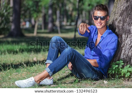 young casual man sitting on the ground next to a tree and pointing at the camera while smiling