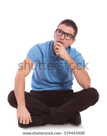 young casual man sitting with his legs crossed and looking away pensively with his hand on his chin. on white background