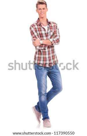 young casual man standing with legs and arms crossed and smilig at the camera, on a white background - stock photo