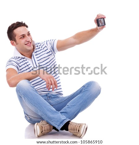 young casual man taking a picture of him self using a smart phone - stock photo