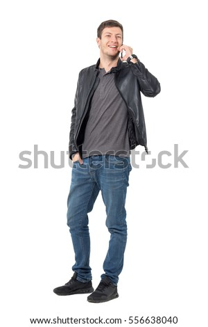 Young casual man talking on the mobile phone laughing and looking at camera. Full body length portrait isolated over white background.