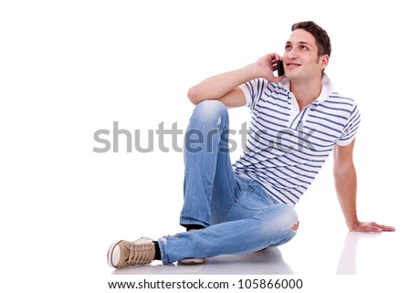 young casual man talking on the phone while lying on the floor - stock photo