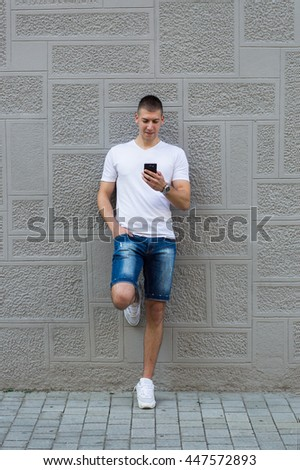 Young casual man using a smart phone texting messages in the street
