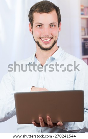 young casual man using laptop smiling. Close up - stock photo