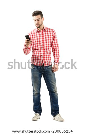 Young casual man using smart phone. Full body length portrait isolated over white background.  - stock photo