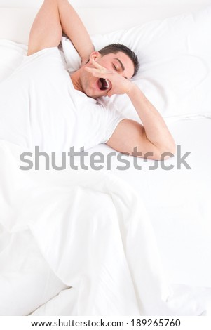 Young casual man waking up in the bedroom and stretches with yawning in bed,  domestic atmosphere