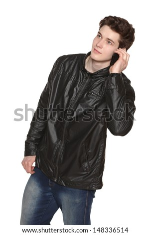 Young casual man wearing black jacket and jeans talking on cellphone while looking up out of frame, against white background - stock photo