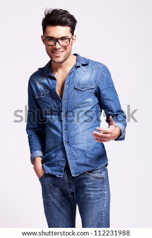 young casual man wearing glasses welcoming you, on gray background - stock photo