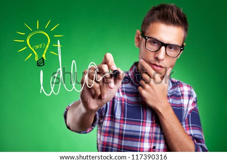 Young casual man wearing glasses,  writing Idea and drawing a light bulb as a symbol for creativity