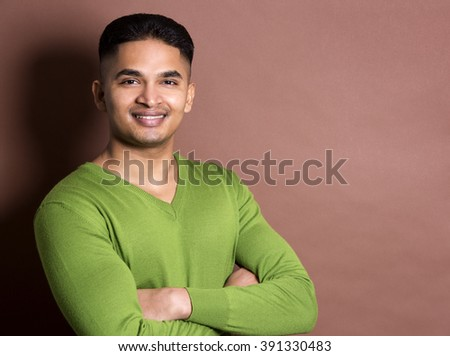 young casual man wearing green on brown background