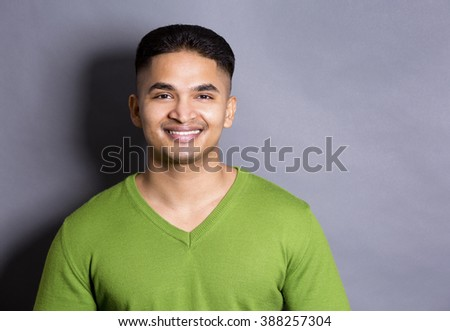young casual man wearing green on grey background