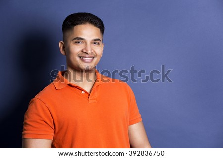 young casual man wearing orange tshirt on blue background - stock photo