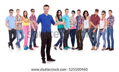 young casual man welcoming to his casual fashion team - stock photo