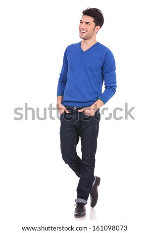 young casual man with hands in pockets looking away from the camera to his side