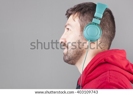 Young casual man with headphones listening to music on grey background