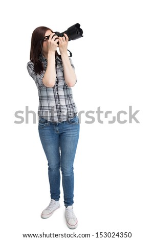 Young casual photographer against white background taking pictures