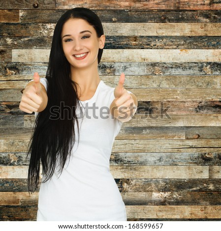 Young casual style woman with blank white t-shirt holds her thumbs up isolated on white background. Woman showing thumb up sign. Focus on the face