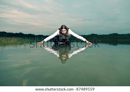 Young casual tough man with long hair and beard standing in lake