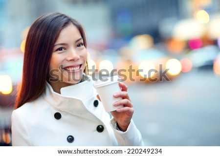 Young casual urban professional woman in New York City Manhattan drinking coffee walking in street wearing coat downtown with yellow taxi cabs in background. Female business woman. - stock photo