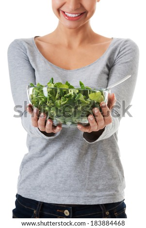 Young casual woman eating lamb's lettuce. Isolated on white.