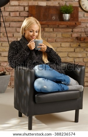 Young casual woman enjoying hot tea at cosy home in armchair. Full size. - stock photo