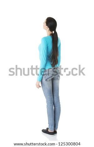 Young casual woman from behind looking up, isolated on white - stock photo