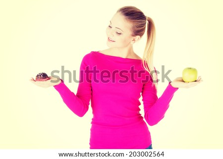 Young casual woman holding an apple and cookie. Isolated on white. - stock photo