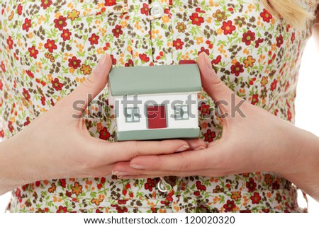 Young casual woman holding house model - stock photo