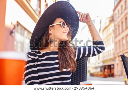 Young casual woman in black with white stripes shirt big summer hat and sunglasses posing at the table in summer cafe. - stock photo