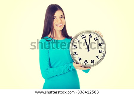 Young casual woman is holding a clock