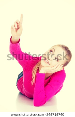Young casual woman lying on belly and pointing up.  - stock photo