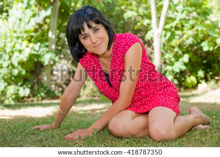 young casual woman posing seated, smiling at the camera, outdoors - stock photo