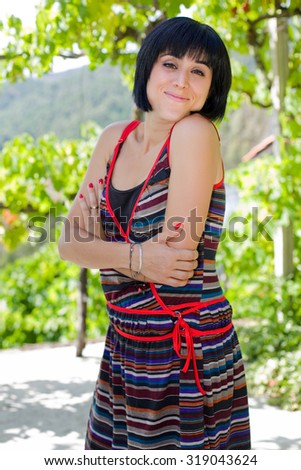 young casual woman posing, smiling at the camera, outdoors - stock photo