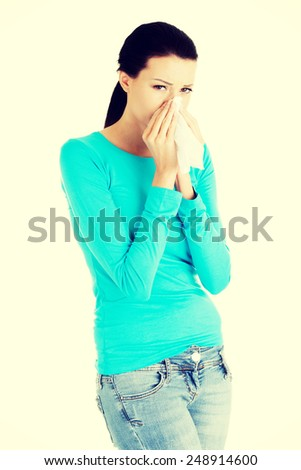 Young casual woman sneezing with tissue.   - stock photo