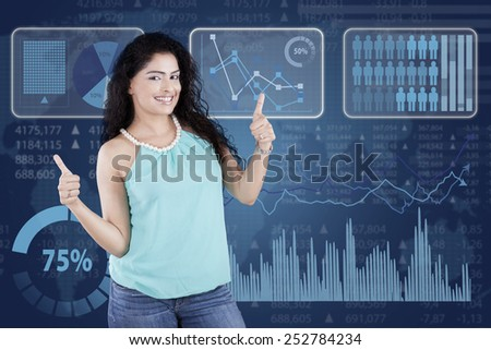 Young casual woman with curly hair standing in front of financial statistics showing thumbs up - stock photo