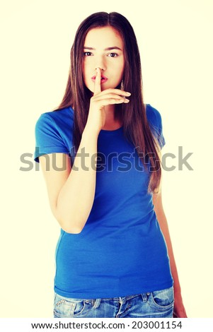 Young casual woman with finger on lips. Isolated on white. - stock photo