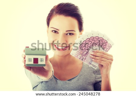 Young casual woman with money and house. - stock photo