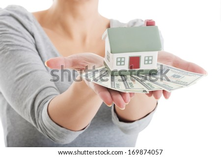 Young casual woman with money and house. Isolated on white.