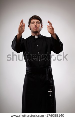 Young catholic priest talking with believers and gesturing - stock photo
