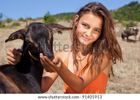 Young cattle girl feeding goats in the Bulgarian mountains - stock photo