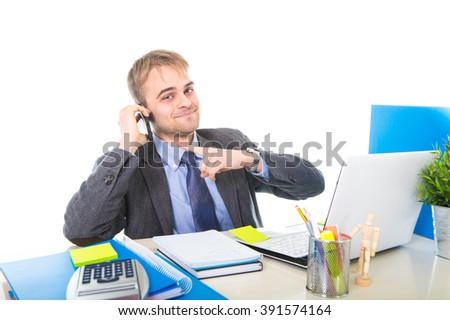 young Caucasian attractive businessman smiling confident talking on mobile phone sitting at laptop computer office desk working happy in business success concept isolated on white background - stock photo