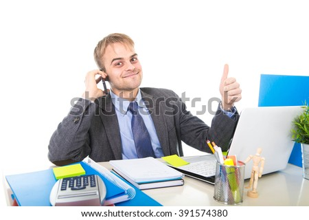 young Caucasian attractive businessman smiling confident talking on mobile phone sitting at laptop computer office desk working happy giving thumb up  in business success concept - stock photo