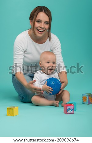 Young Caucasian attractive smiling mother playing with her cute little son with a ball and colored blocks, baby boy wearing bodysuit, mom embracing baby, isolated on blue - stock photo